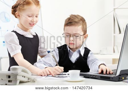 Little boy and girl working together in office