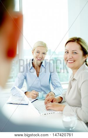 Two women listening to their boss and smiling, the focus is on the youngest