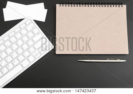 Blank brown notebook, keyboard, pen on black table background. can be used for your text or artwork / Top view