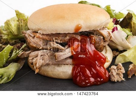 hamburger with pulled pork fresh healthy salad and ketchup on slate