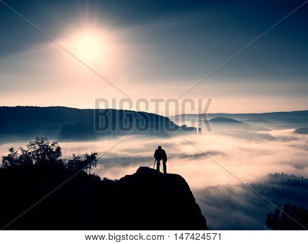 Professional Photographer On Location Takes Photos With Mirror Camera On Peak Of Rock.