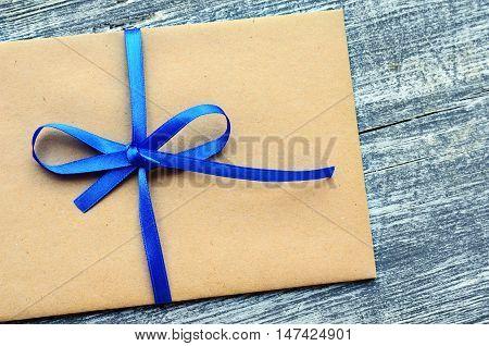 Kraft envelope tied with a blue ribbon on a wooden background. Gift envelope. Homemade kraft paper envelope