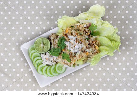 Fried rice with crab topped streamed crab,halve green lemon,sliced cucumber,lettuce and coriander  on gray. Top view