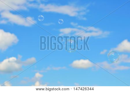 Soap bubbles are flying against the blue sky and white clouds