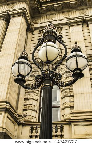 Historical sandstone building with Roman columns and antique street lamps