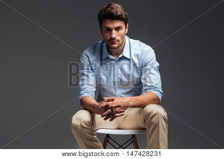 Relaxed casual handsome man in blue shirt sitting on the chair over grey background