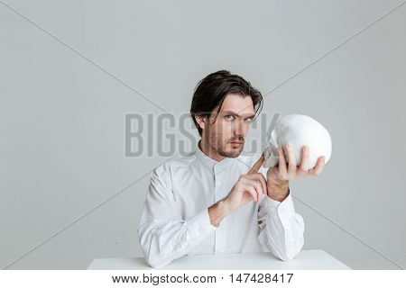 Bristled man sitting at the table and pointing finger at fake skull in hands isolated on the gray background