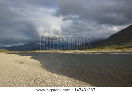 Cloudy sky over the Ural mountains and mountain river. Journey through the Polar Urals.