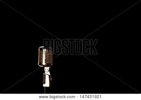 Old retro microphone on a black background