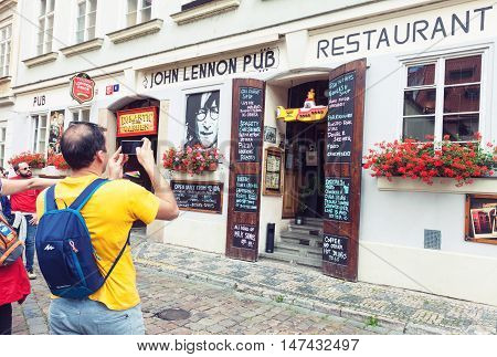 PRAGUE CZECH REPUBLIC - JUNE 27 2016: Tourists taking pictures of John Lennon pub entrance in Prague Czech Republic