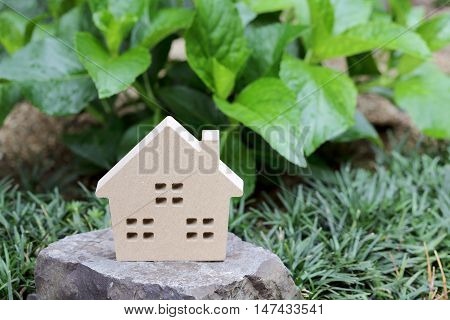 Wooden toy house on stone, green background