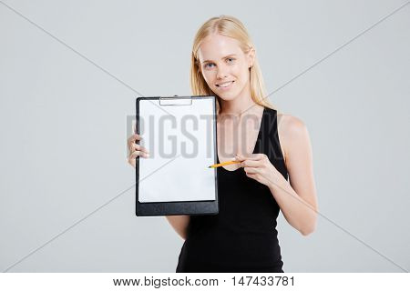 Smiling businesswoman pointing at blank clipboard isolated on a white background