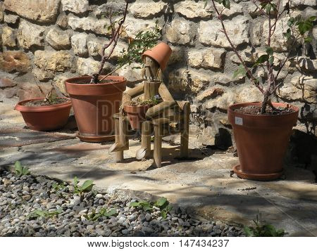 puppet between flowerpots outside of a house