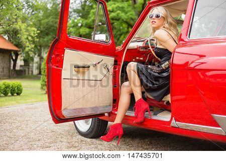 Sexy woman sitting in red retro car