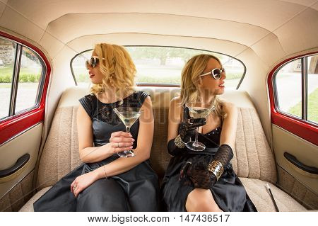 Two women sitting in vintage car and having coctails