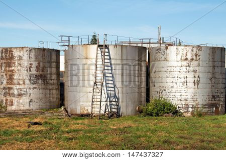 Old industrial storage tank with stairs against a blue sky