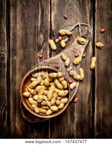 Peanuts in a wooden bowl . On wooden background.