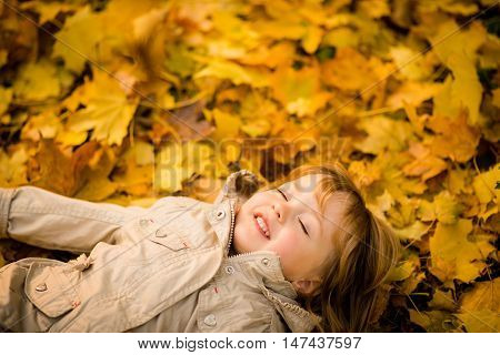Little child daydreaming with closed eyes lying in fallen leaves in autumn