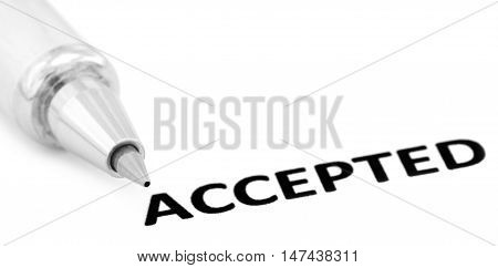 ACCEPTED written in a white paper with a silver ballpoint