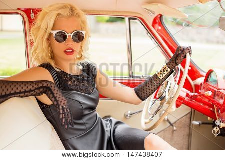 Sexy vintage style woman driving a retro car