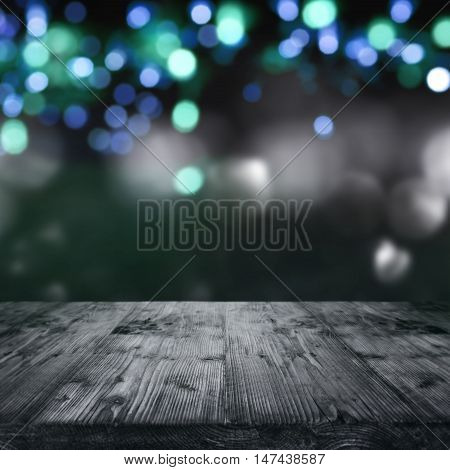 Dark halloween party background with lights in front of a wooden table