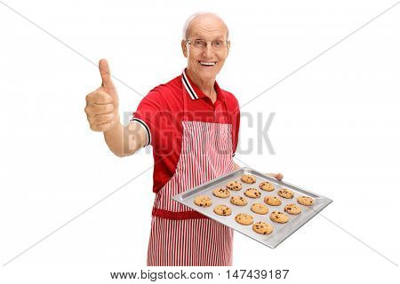Joyful elderly man holding a tray of freshly baked cookies and giving a thumb up isolated on white background