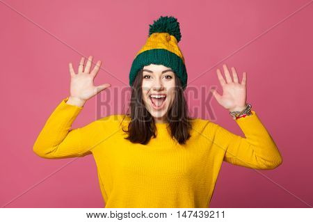 Happy smiling young girl wearing yellow pullover holding hands up. Cheerful hipster girl on bright pink background.