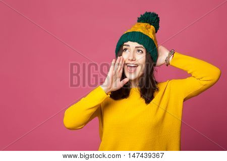 Cute young girl in colorful warm clothes shouting against pink wall. Teenage girl wearing a hat call out with copy space.