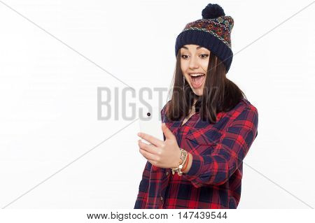 Cheerful girl wearing a hat taking a self portrait with a cell phone. Isolated on white.