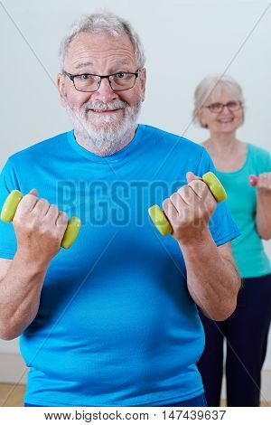 Senior Couple In Fitness Class Using Weights