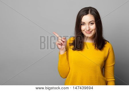 Beautiful young woman pointing her finger towards blank space isolated over grey background