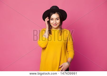 Trendy sexy young female wearing casual clothes posing over pink background
