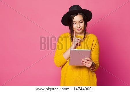 Beautiful young fashionable woman using tablet computer over pink background