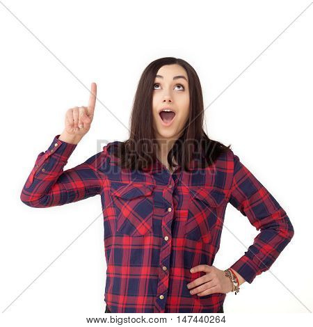 beautiful and surprised young brunette woman looking into the camera and pointing up. Open mouth and hand with finger pointing up. Isolated on white background.