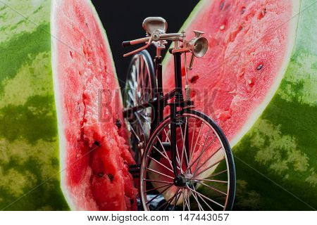 Little model of a retro vintage bicycle near a big cut in half scarlet ripe watermelon