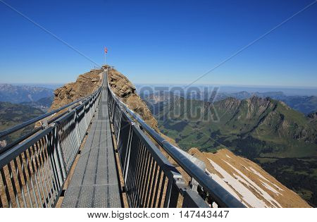 Scene on the Sex Rouge Swiss Alps. Suspension bridge connecting two mountain peaks. Popular travel destination.