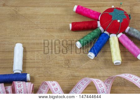 Red pincushion and several colourful threads as a sun and two treads as a boat on the light wooden background