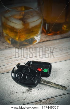 Car keys glass of whiskey in background. Drinking and driving