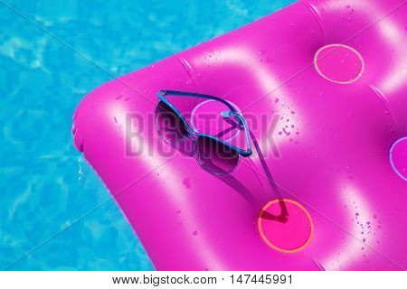 Sunglasses With Pink Mattress At The Swimming Pool