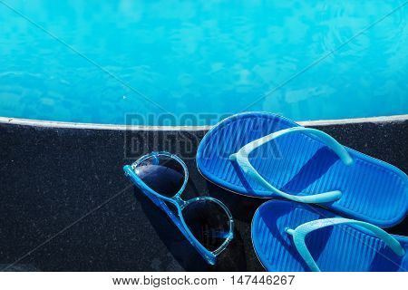 Blue Slippers And Sunglasses On Border Of A Swimming Pool