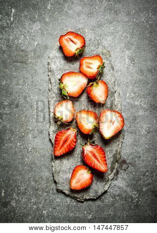 Ripe halved strawberries. On the stone table.