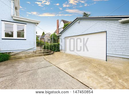 Separate Garage With Blue And White Trim And Driveway.