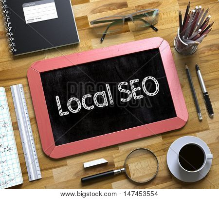 Local SEO on Small Chalkboard. Local SEO - Red Small Chalkboard with Hand Drawn Text and Stationery on Office Desk. Top View. 3d Rendering.