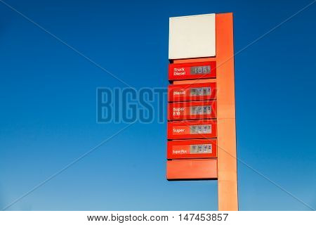 a red gas station price sign on blue background