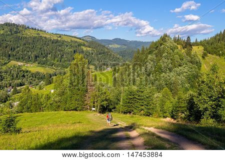 Tourist descend from the mountains to the valley Carpathians Ukraine Nature landscape