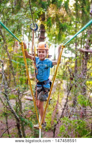 boy enjoys zip line. joyful child on a height in the high wire park. looking at camera