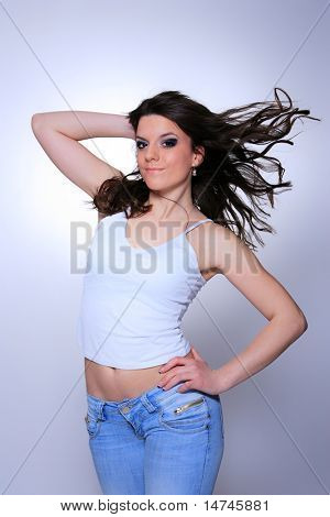 smiling young woman in jeans and t shirt, studioshot over neutral background
