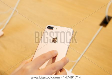 PARIS FRANCE - SEPTEMBER 16 2016: New Apple iPhone 7 Plus being tested by woman after purchase - woman looking at new double camera. New Apple iPhone tends to become one of the most popular smart phones in the world in 2016