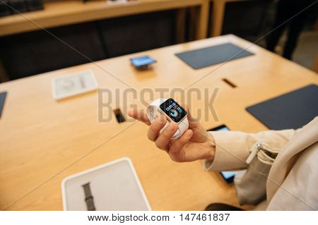 PARIS FRANCE - SEPTEMBER 16 2016: New Apple Watch Series 2 tested by woman after purchase - looking at the new strap activity app. New Apple Watch tends to become one of the most popular wearable device in 2016