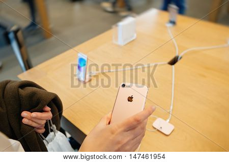 PARIS FRANCE - SEPTEMBER 16 2016: New Apple iPhone 7 being tested by woman after purchase - woman looking at new iSight camera. New Apple iPhone tends to become one of the most popular smart phones in the world in 2016
